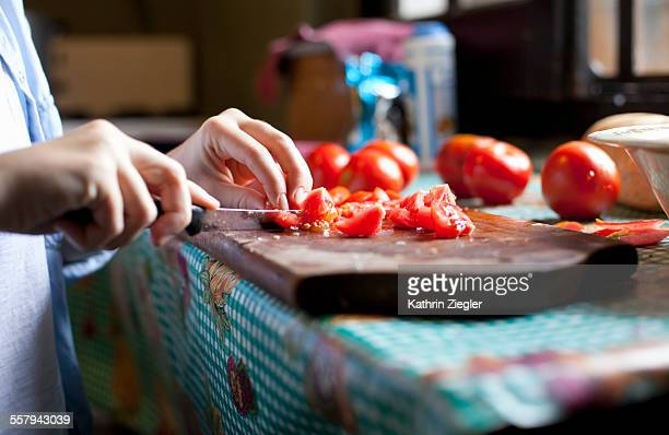 woman cutting tomatoes, close-up of hands