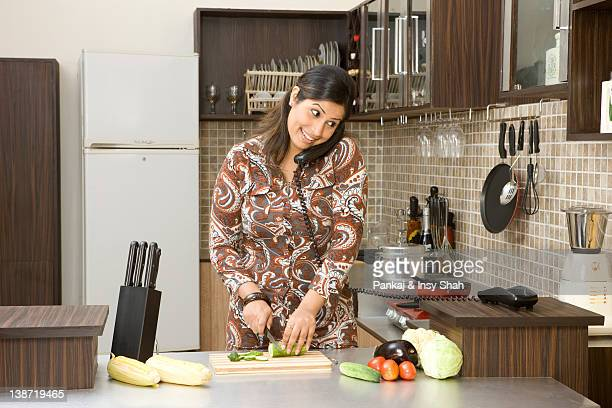 Woman cutting vegetables while talking on the phone in the kitchen