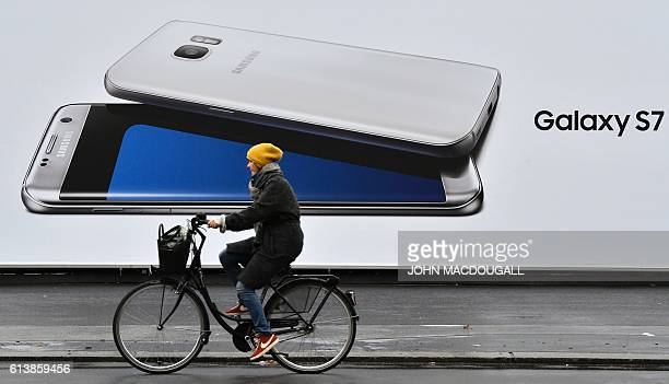 A woman cycles past a billboard advertising the Samsung's Galaxy S7 Edge smartphone on October 11 2016 in Berlin The world's largest smartphone maker...