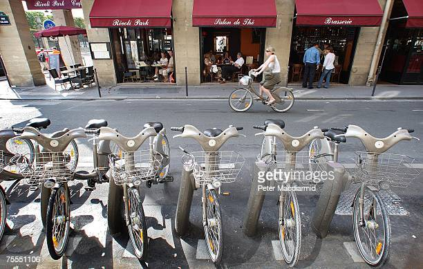A woman cycles past a row of 'Velib' rental bicycles on July 19 2007 in central Paris The new scheme uses 20000 heavy duty bicycles which can be...