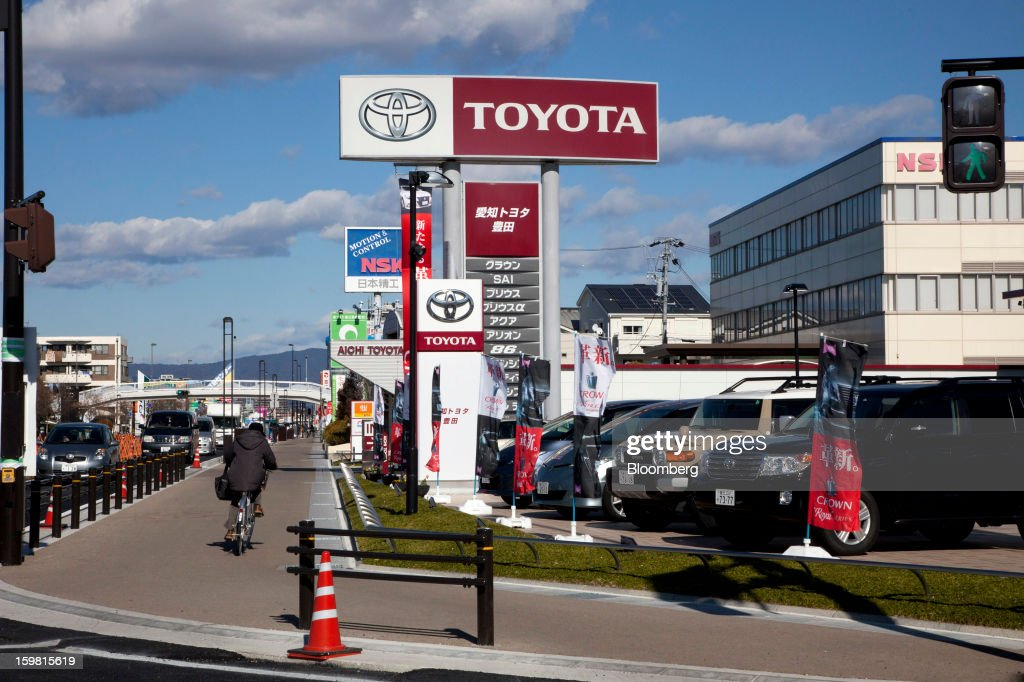 A woman cycles past a Toyota Motor Corp. dealership in Toyota City, Aichi Prefecture, Japan, on Friday, Jan. 18, 2013. Toyota, poised to regain its title as the world's biggest carmaker this year, said last month its vehicle sales may rise 2 percent next year to a record, led by demand from overseas markets. Photographer: Tomohiro Ohsumi/Bloomberg via Getty Images