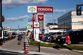 A woman cycles past a Toyota Motor Corp dealership in Toyota City Aichi Prefecture Japan on Friday Jan 18 2013 Toyota poised to regain its title as...