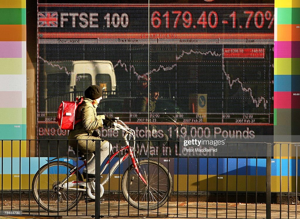 A woman cycles past an electronic sign displaying stock price information on February 28, 2007 in London. World stock prices have tumbled after uncertanties in the Chinese stock market.