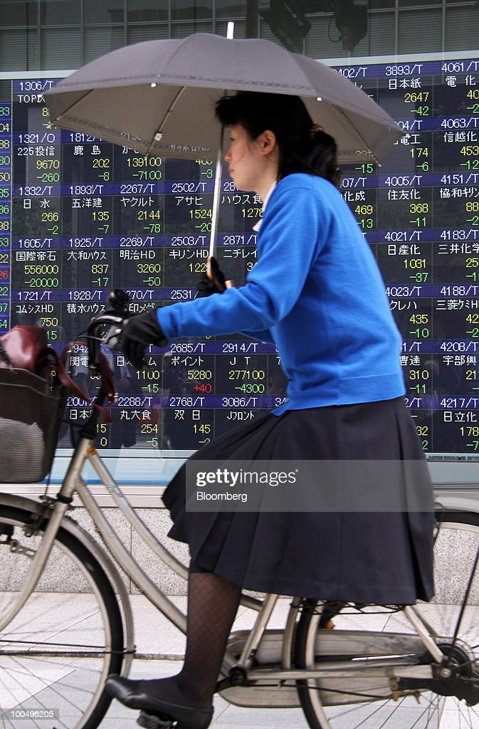 A woman cycles past an electronic stock board outside a securities firm in Tokyo, Japan, on Tuesday, May 25, 2010. Japanese stocks fell, dragging the Nikkei 225 Stock Average to its lowest close in almost six months on growing signs European financial institutions are facing stress and as the yen rose against the euro and dollar. Photographer: Haruyoshi Yamaguchi/Bloomberg via Getty Images