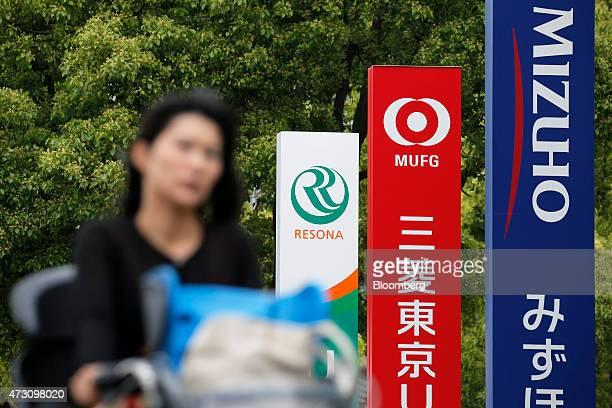 A woman cycles past signage for Mizuho Bank Ltd right Bank of Tokyo Mitsubishi UFJ Ltd center and Resona Bank Ltd in Tokyo Japan on Tuesday May 12...