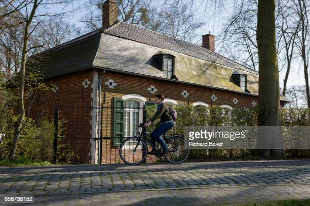 A woman cycles past the gamekeeper's house at the entrance of the privatelyowned de Merode Castle on 25th March in Everberg Belgium The gamekeeper's...