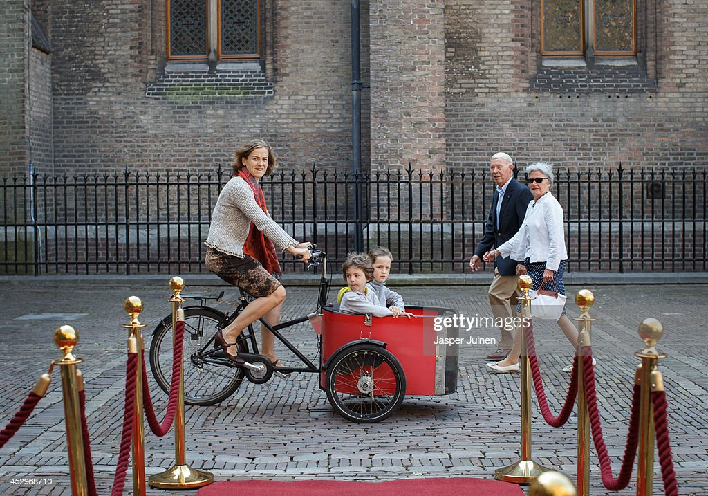 A woman cycles with two children on a carrier tricycle past the place where Malaysian Prime Minister Najib Razak will arrive to meet with Dutch Prime...