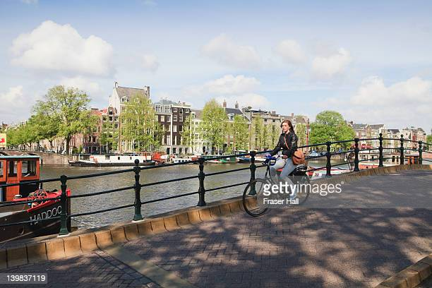 Woman cycling alongside Amstel River, Amsterdam, Netherlands