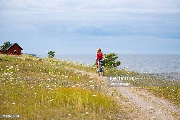 Woman cycling at coast