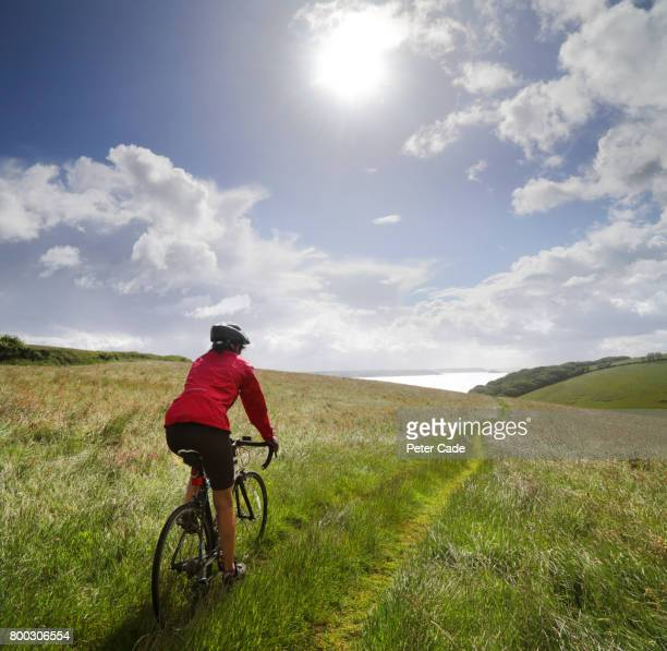 Woman cycling in field on sunny day