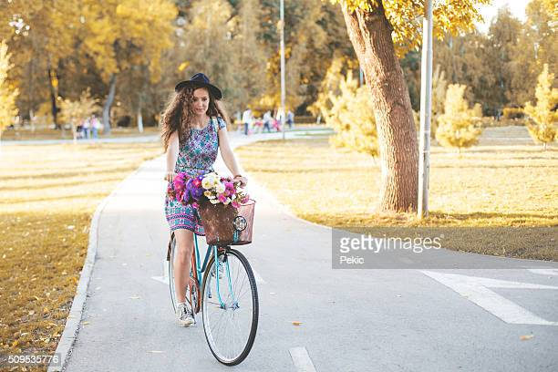 Woman cycling on bicycle, sunset autumn park exercising