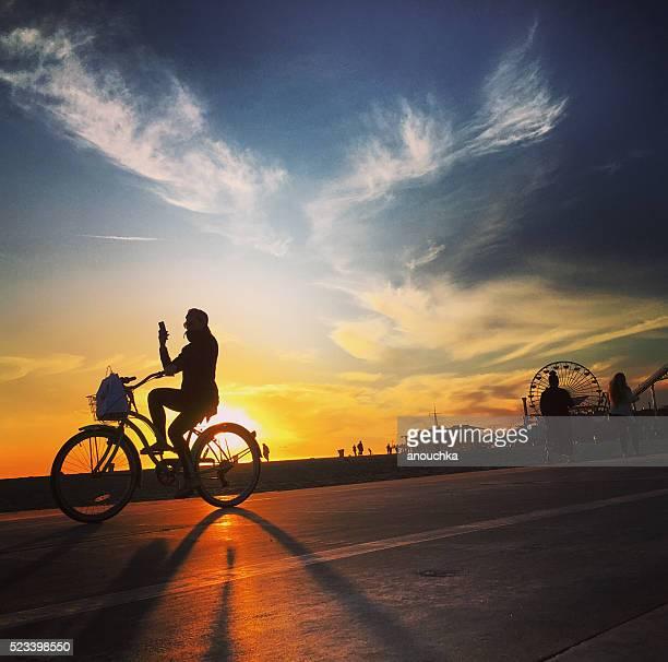 Woman cycling on Santa Monica beach taking photos