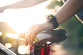 woman cyclist hand with smart watch on saddle bicycle at summer trail. All on screen are design up.
