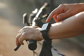 Woman cyclist hands with heart rate icon on smart watch, bicycle at summer trail. All on screen are design up.