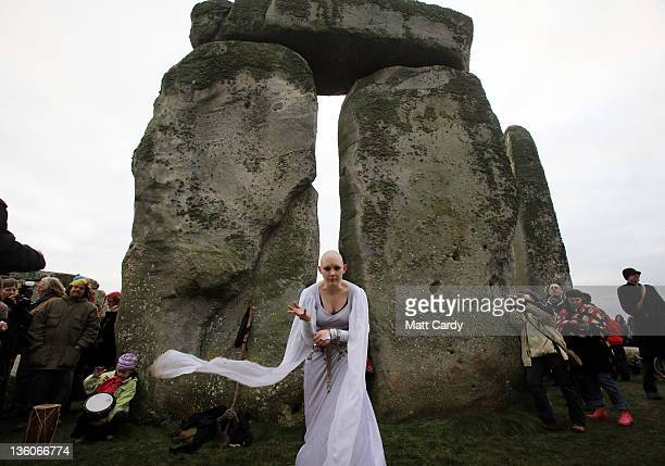 A woman dances as druids pagans and revellers take part in a winter solstice ceremony at Stonehenge on December 22 2011 in Wiltshire England The...
