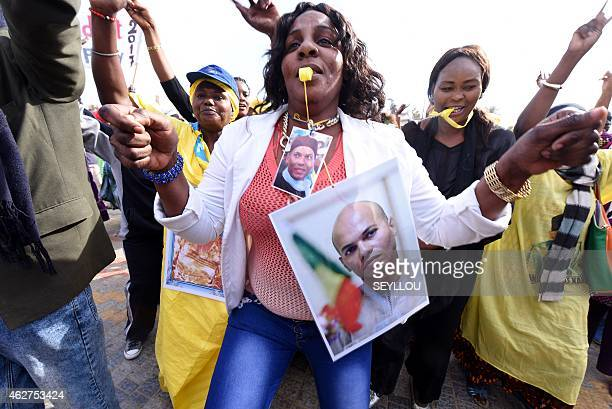 A woman dances as she wears pictures of Karim Wade former minister and son of former Senegalese president Abdoulaye Wade during a meeting of the...