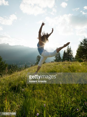 Woman dances in mountain meadow, sunrise : Stock Photo