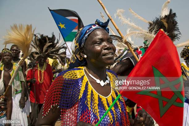 A woman dances with a Moroccan flag during a welcoming ceremony for The King of Morocco on February 1 at Juba airport at the start of his two day...