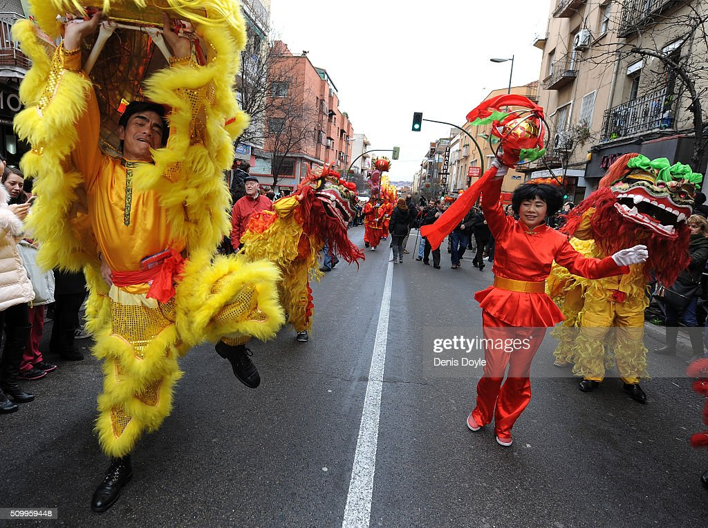 A woman dances with dragons during the procession to celebrate The Year of The Monkey on February 13, 2016 in Madrid, Spain. The Madrid Town Hall organised this year's lunar year celebrations for the first time in Madrid's Chinatown district of Usera.