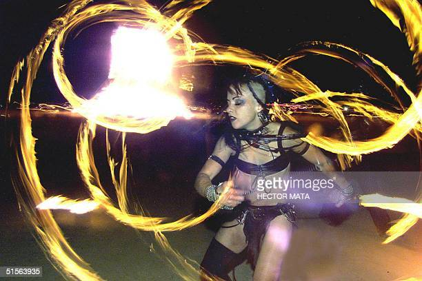 A woman dances with fire during the final day of the Burning Man Festival in Nevada early 03 September 2000 The festival is a spontaneous encounter...