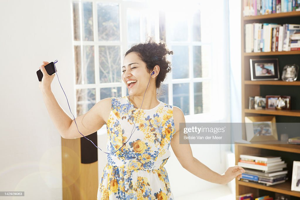 Woman dancing and singing in livingroom.