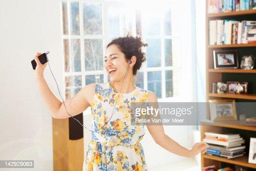 Woman dancing and singing in livingroom. : Stock-Foto