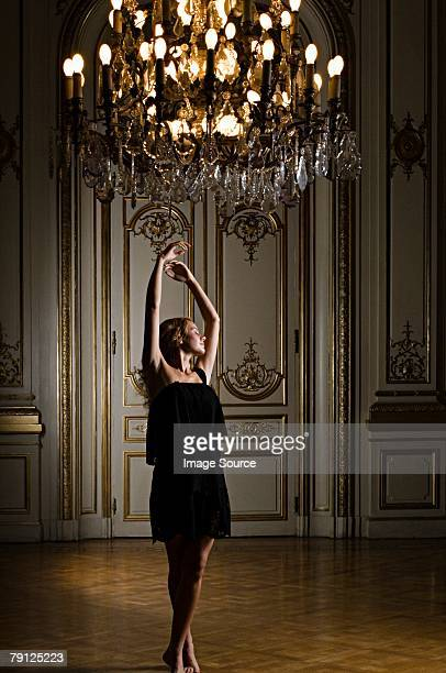 Woman dancing beneath chandelier