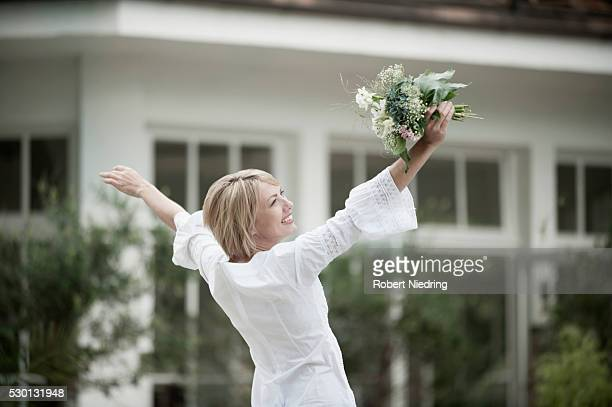 Woman dancing excited holding wedding bouquet