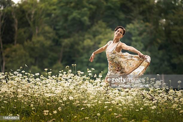A woman dancing in a field of wild flowers.