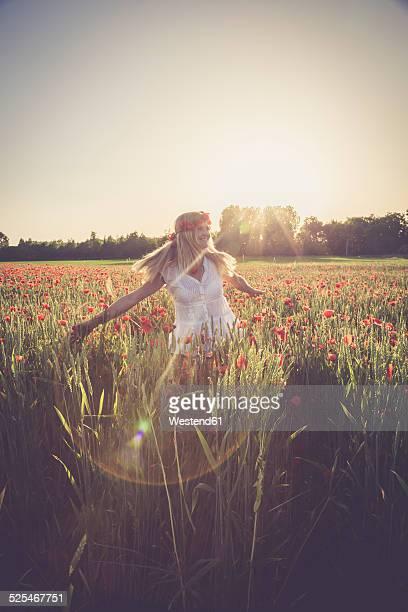 Woman dancing in a poppy field at back light