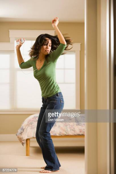 Woman dancing in bedroom while listening to music