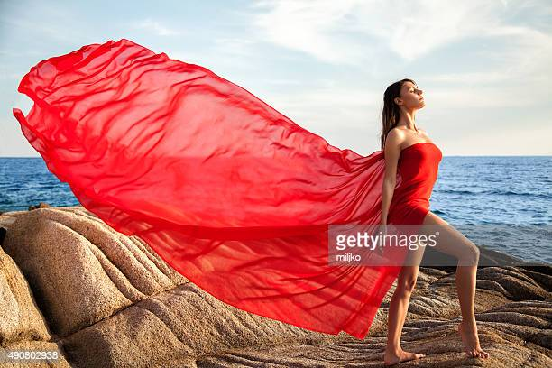 Woman dancing in red dress that flying on the wind