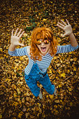 Happy, young woman dancing in the forest covered with autumn leaves.