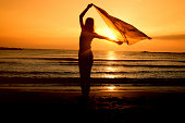 Woman dancing on the beach at sunrise