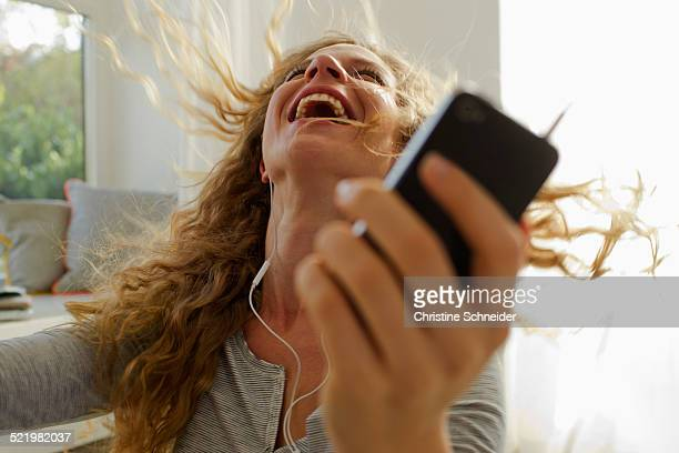 Woman dancing to music on smartphone
