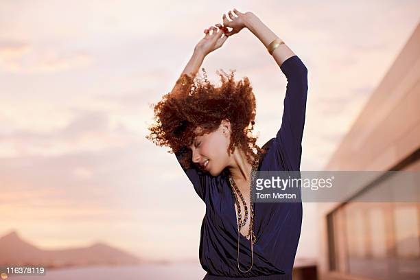 Woman dancing with arms raised