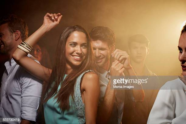 Woman dancing with friends in nightclub