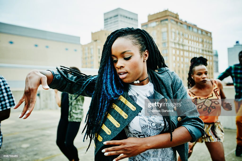 Woman dancing with friends on rooftop : Stock Photo