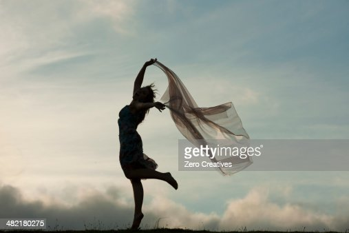 Woman dancing with sheer fabric over head : Stock Photo