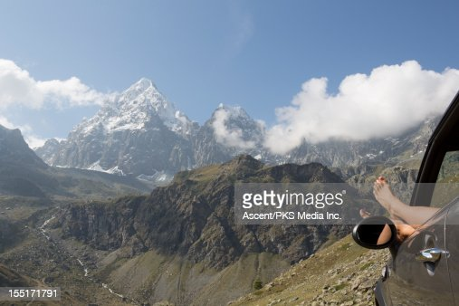 Woman dangles feet out of car window, snowy mtns : Stock Photo