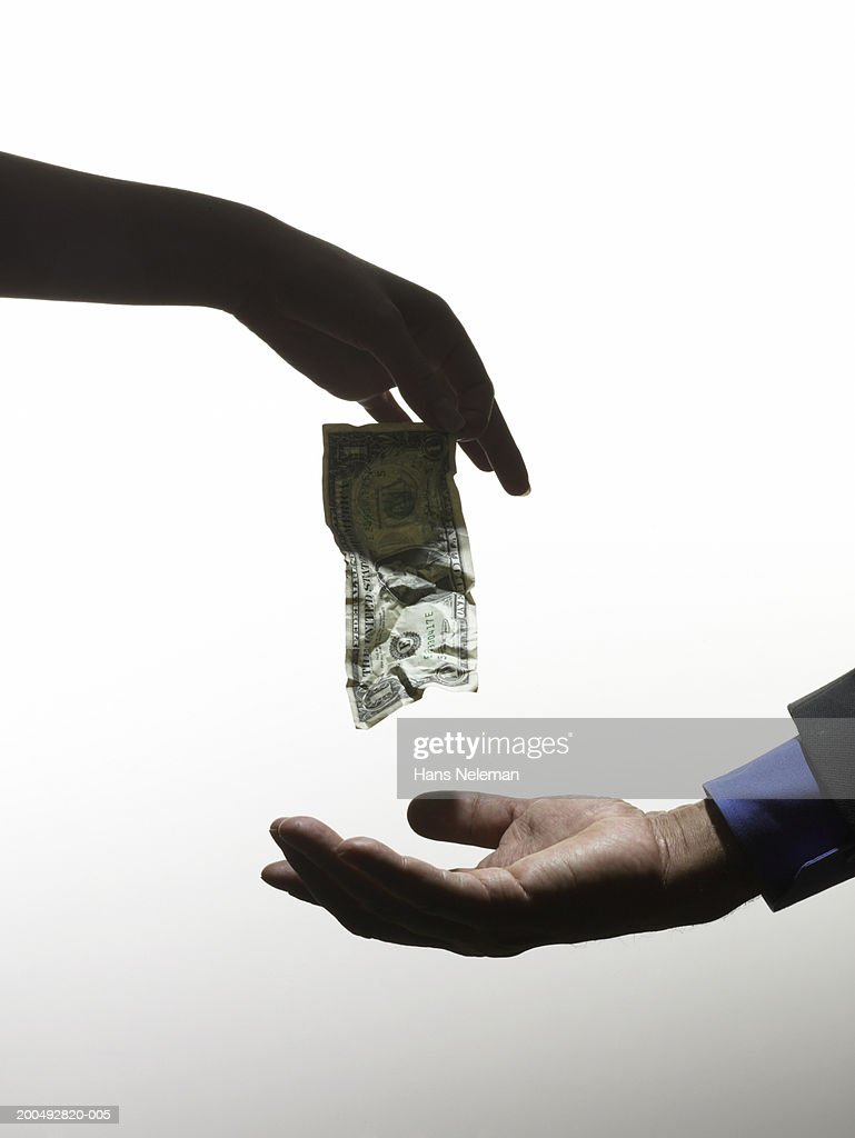 Woman dangling crumpled banknote above man's palm, close-up, side view : Stock Photo