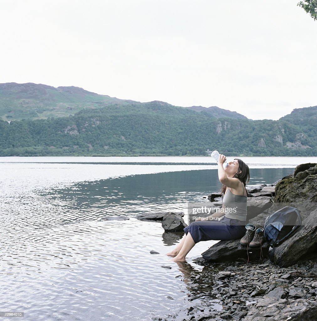 Woman dangling feet in lake and drinking from water bottle : Stock Photo