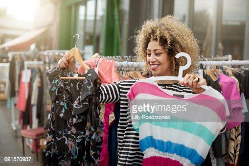 Woman deciding between two dresses at market