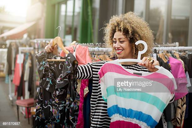 Woman deciding between two dresses at market