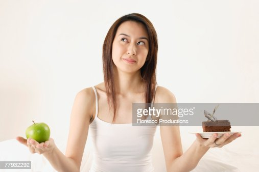 Woman deciding on piece of cake or apple : Stock Photo