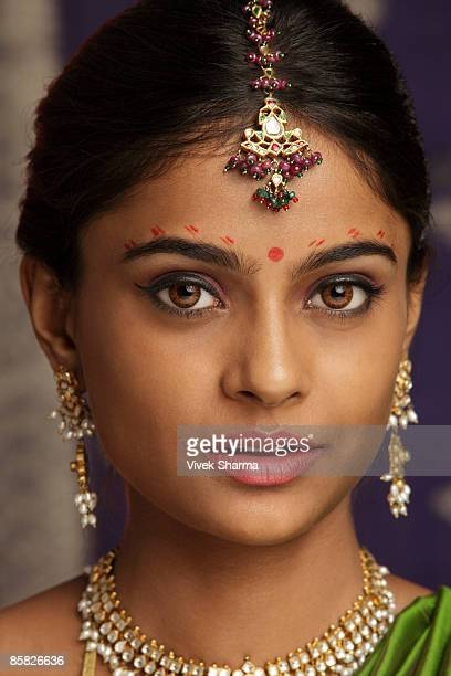 woman decorated with henna tattoos, jewelry and bindi