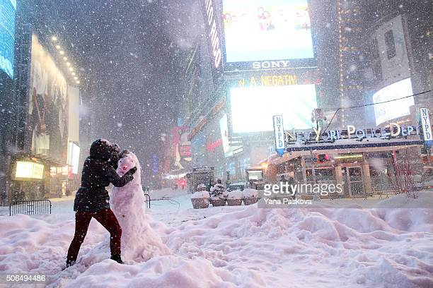 A woman decorates a snowman in Times Square as all cars but emergency vehicles are banned from driving on the road on January 23 2016 in New York...