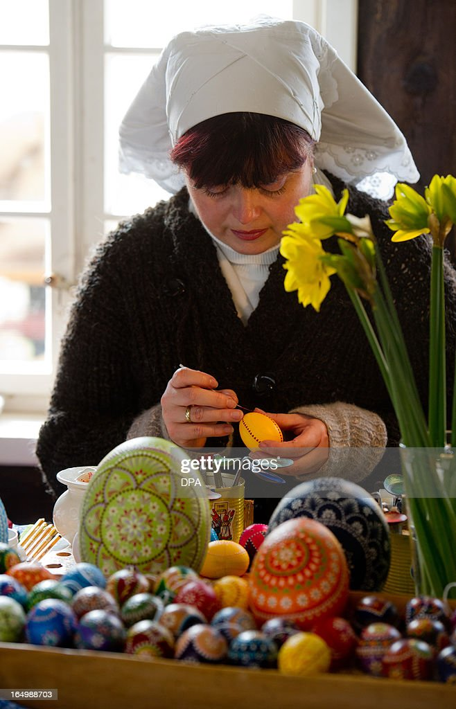 A woman decorates Easter eggs in the museum 'Spreewalddorf' in Lehde, eastern Germany, on March 30, 2013. Tourism starts in the Spreewald region on Easter saturday. AFP PHOTO / PATRICK PLEUL GERMANY OUT