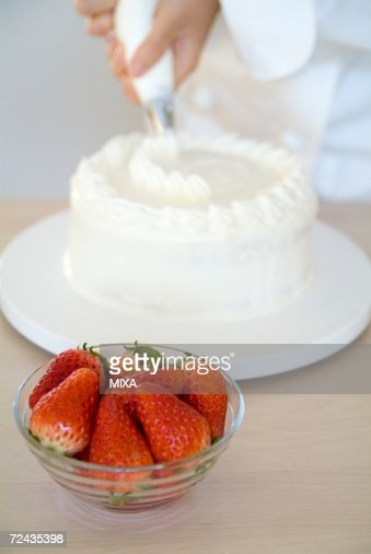 Cake Decoration By Cream : A Woman Decorating A Cake With Whipped Cream Stock Photo ...