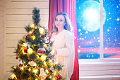 Woman decorating a Christmas tree. Christmas home room with tree and moon lighting in window. The elements of this image furnished by NASA.